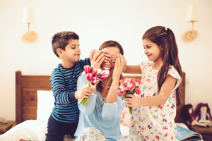 Kids giving their mother flowers to surprise her on Mother's Day