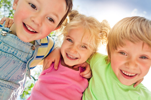 Three happy children playing in summer