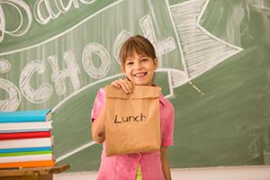Schoolgirl holding sack lunch in classroom