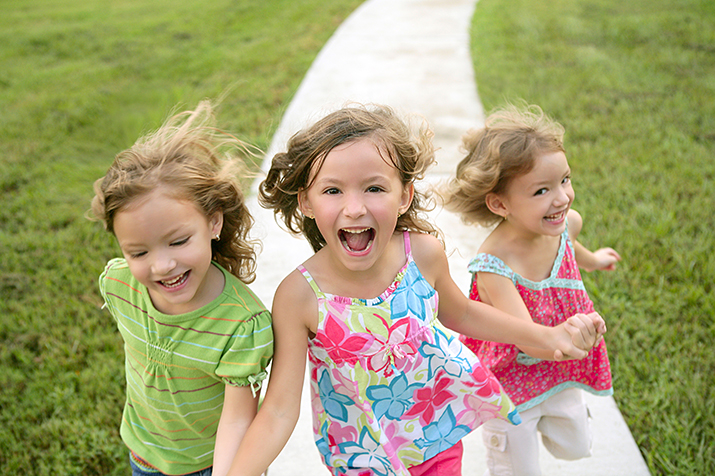 Smiling Young Girls Running On Sidewalk